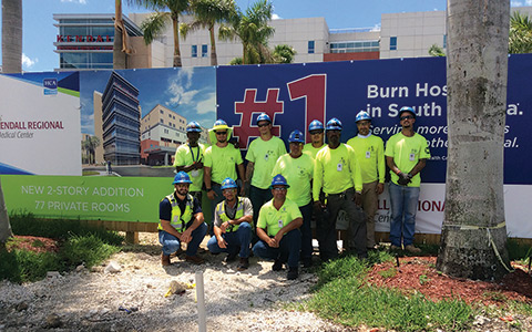 A team of construction workers outside posing for a photo